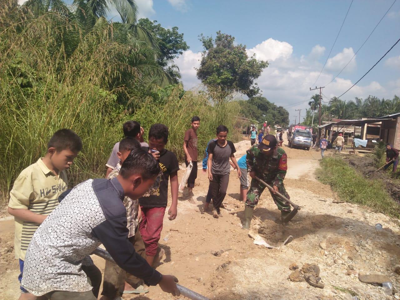 Babinsa Koramil 05/PB dan Masyarakat di Paluta Gotong Royong Perbaiki Jalan Rusak Sejauh 4 Km