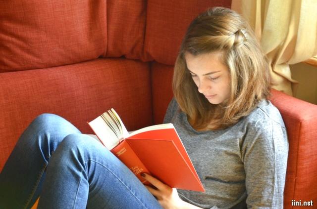 ảnh cô gái đang ngồi ghế đọc sách