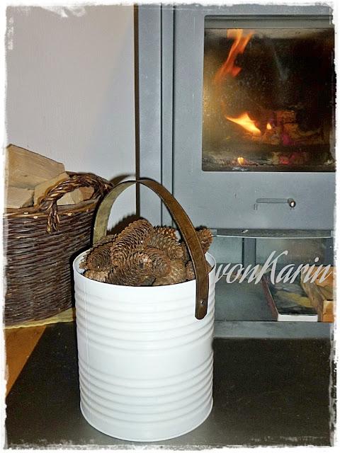 Weisser Konservendosen-Eimer mit Lederhenkel vor Kaminofen
