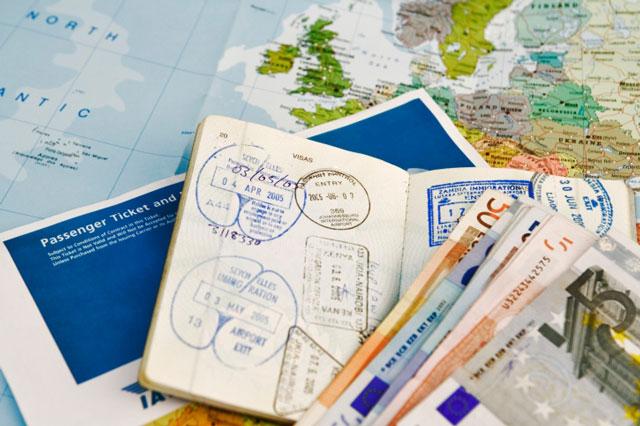 Mapa mundial aberto com passaporte, passagem e dinheiro em cima.