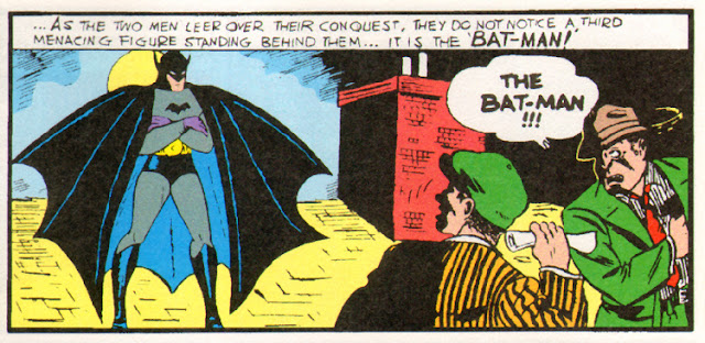 Batman stands on a roof arms crossed frighting two criminals