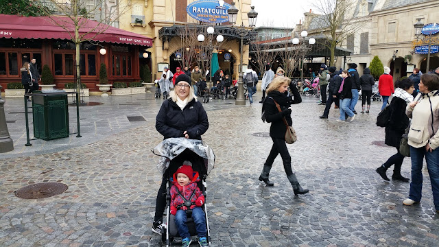 Little boy in a pushchair with his Mum standing behind it and the Ratatouille area in the background