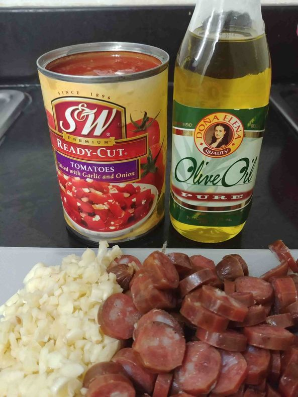 Olive oil, tomatoes, garlic, and chorizo for the pasta recipe