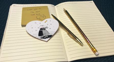 "Note with text ""Love you to the moon and back"" on David Tlale stationery"