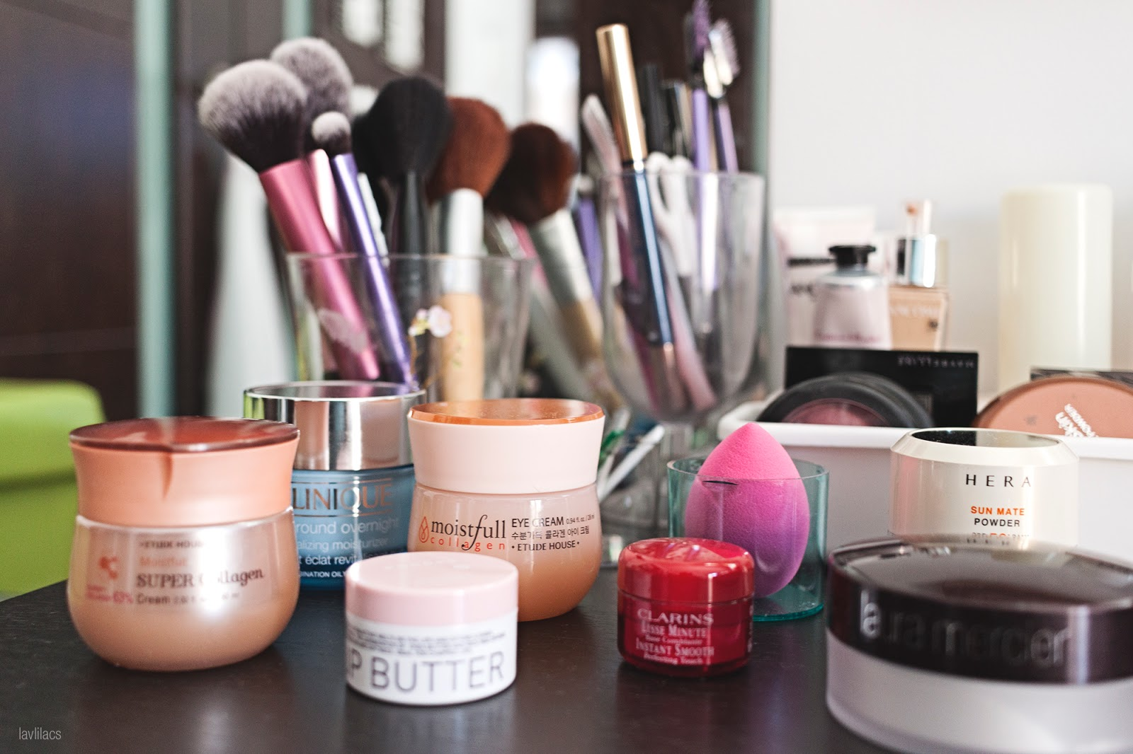 Daily jarred skincare products and makeup brushes on top of bedside table
