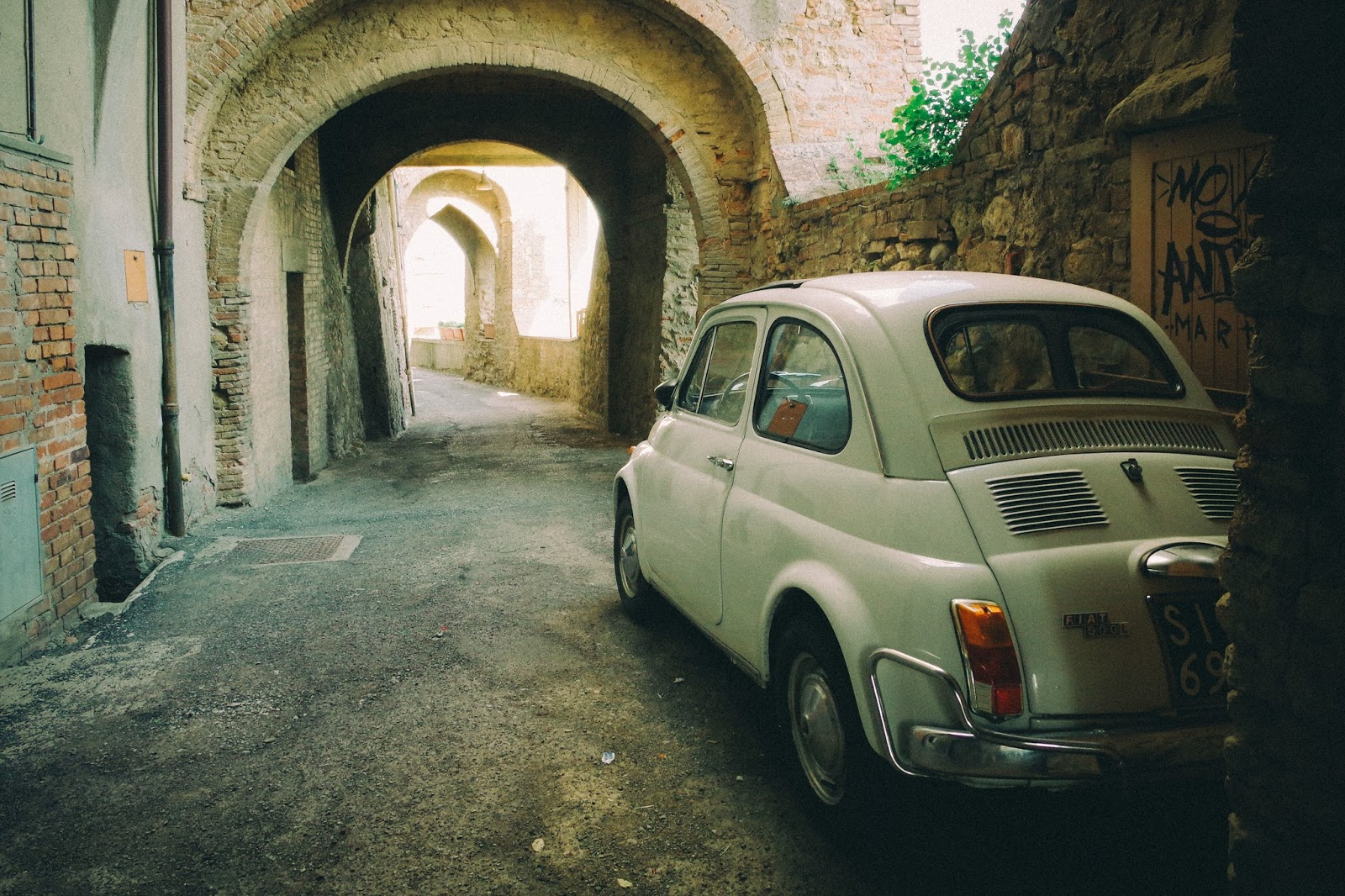 Travelling by car safely - Fiat driving through old arches in a town in Italy