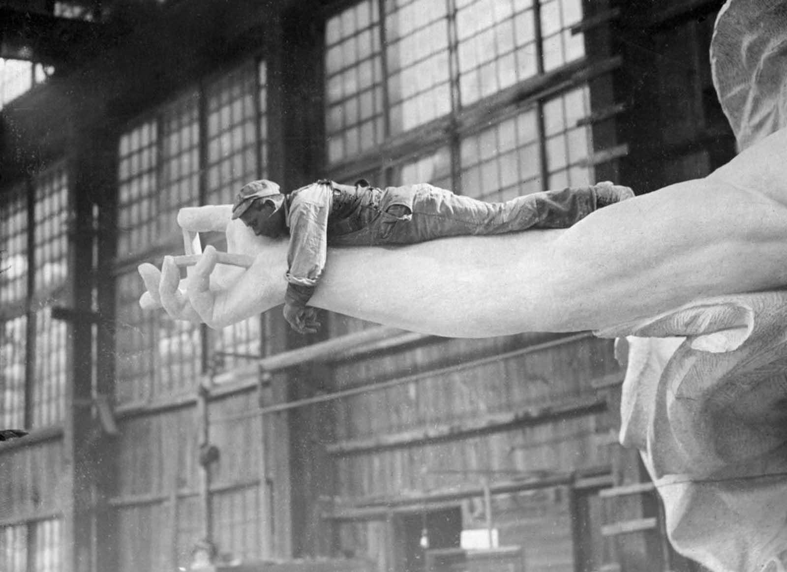 Un trabajador yace sobre el brazo de once metros de Mercury, que forma parte de las estatuas de Grand Central Station.