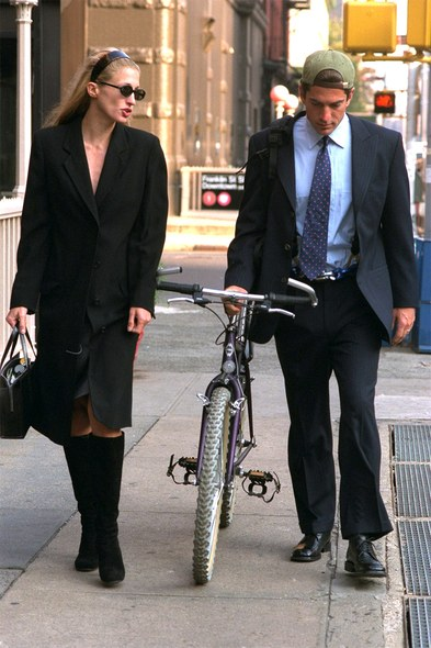 woman in black coat and boots walking with a man pushing a bike.