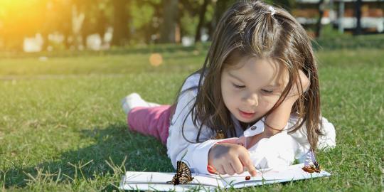 foto anak kecil sedang membaca buku