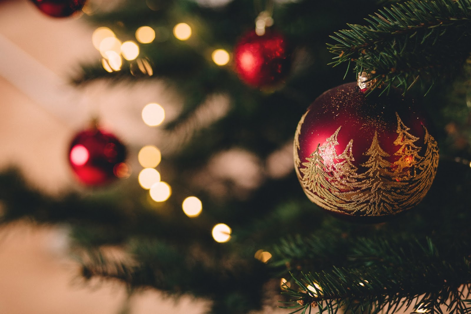 A close up photo of part of a Christmas tree, decorated in white lights and red baubles. The focus is on the branches and a bauble on the right, closest to the camera, with a number of fir trees painted on the baulble in gold glitter. The branches, baubles and lights in the distance, on the left, are out of focus.