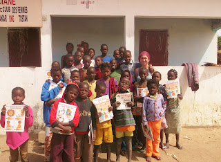 Lucy (top right) with village kids holding up their new Tostan children's books.