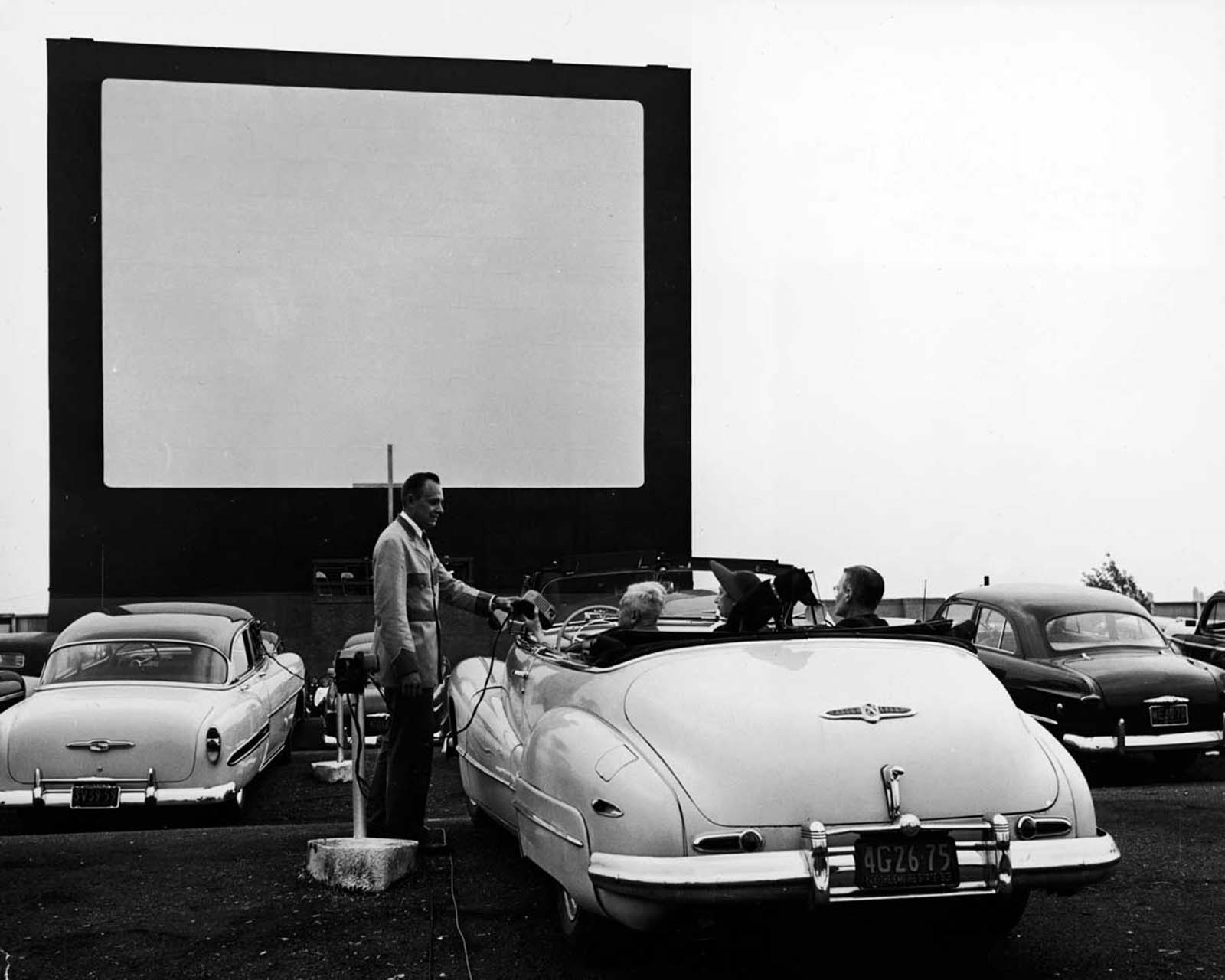 A uniformed drive-in theater attendant hands a clip-on speaker to the driver of a convertible while the car's other passengers watch, New York, early 1950s.