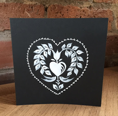 A black greetings card painted decorated with a white traditional folk art design against a brick wall.