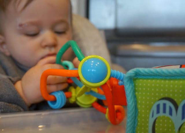 baby playing with toys in high chair