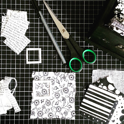 Flat lay of various black and white fabrics, scissors, pen and templates laid out on a cutting mat.