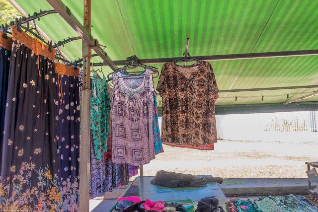 banca na feira com roupas penduradas para vender