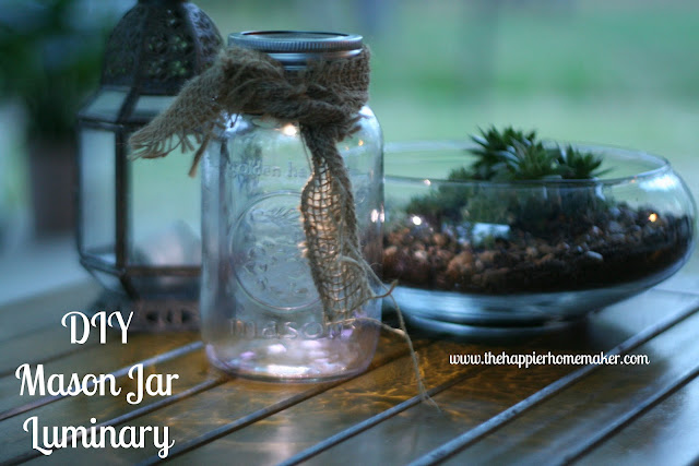 A close up of a DIY glass jar luminary with burlap ribbon next to a succulent plant