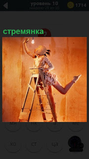 В комнате девушка закручивает лампочку находясь на стремянке