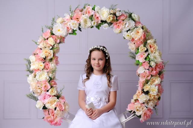 Piękna kwiecista dekoracja sesji fotograficznej dziewczynki w ubraniu komunijnym