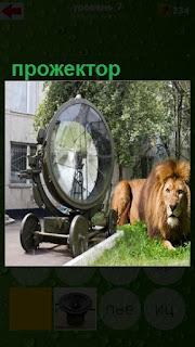 на улице стоит огромный прожектор и рядом ходит лев