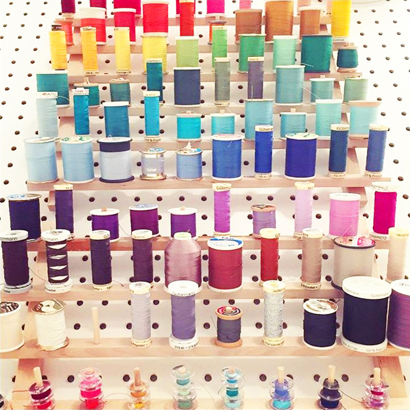 organize thread on pegboard in sewing room