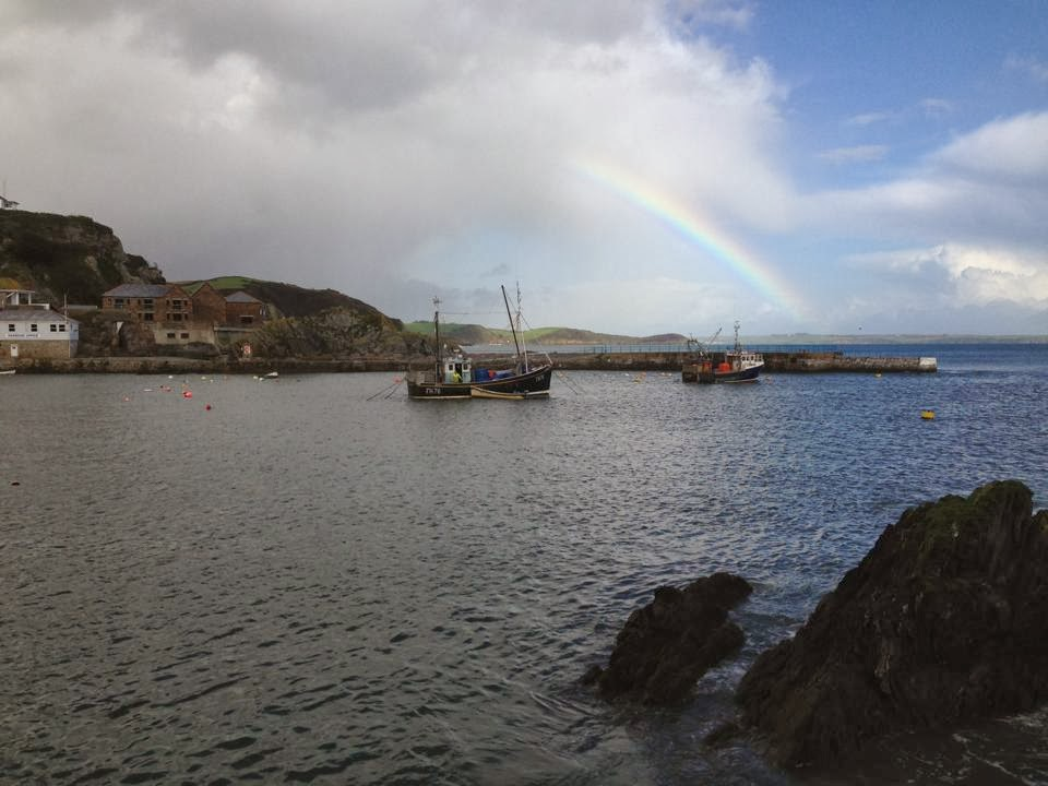 A rainbow over the jetty at Mevagissey. The sea can be seen on the foreground with a few boats scattered on the water