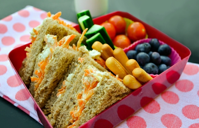 vegan kids lunchbox including hummus and carrot sandwiches, blueberries, breadsticks and cucumber and cherry tomatoes