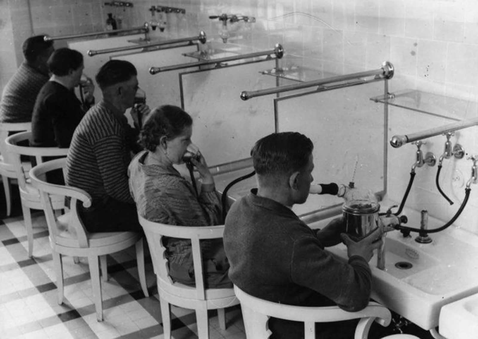 Pacientes en un hospital en Alemania que inhalan medicamentos en polvo como el mentol y el eucalipto para curar enfermedades respiratorias, alrededor de 1930.