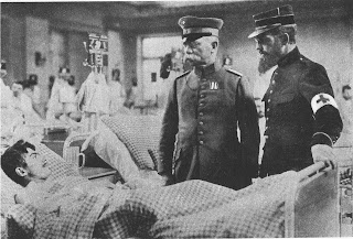 Black and white photo of a military hospital with a man lying on a bed in the very front of the photo. Slightly right to the man are standing two military generals. One on the right is wearing a German military uniform and another one on the right is wearing a French military uniform with a cross symbol on his arm. Behind these three men are nurses and other patients going in and out of the room.