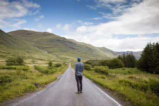 Homme regardant le sentier qui se perd à l'horizon