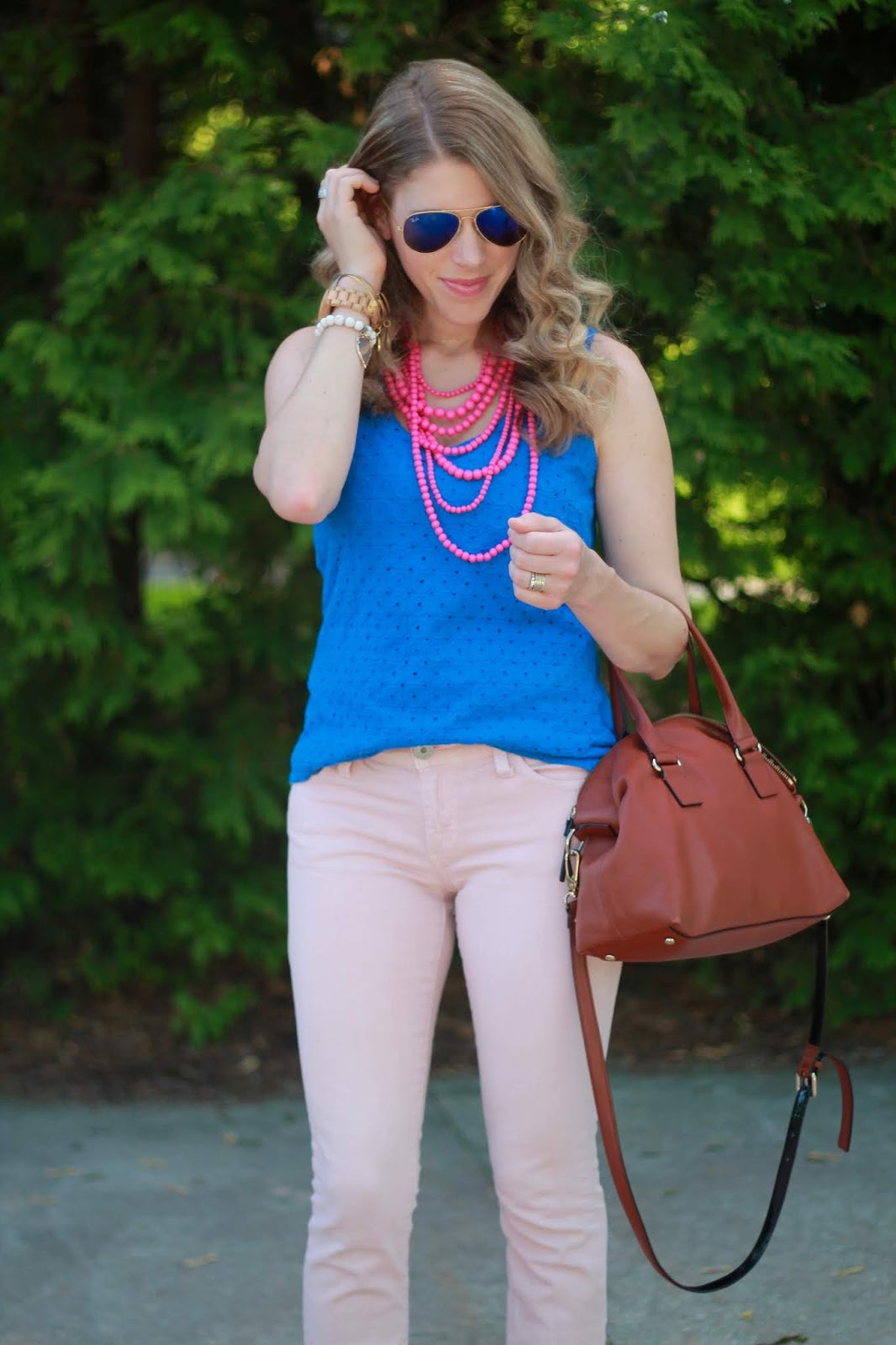 blue eyelet top, blush jeans, pink beaded necklace, cognac accessories
