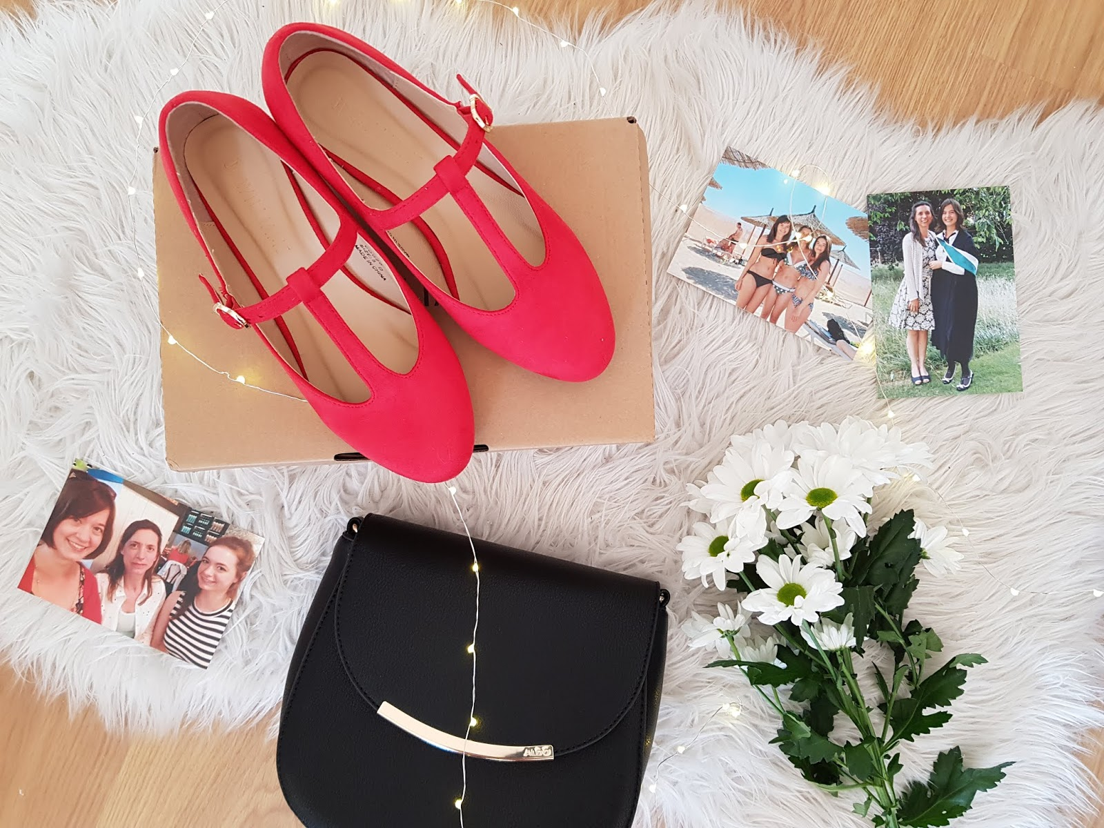 flatlay featuring red heeled shoes, flowers, family photos, and a black handbag