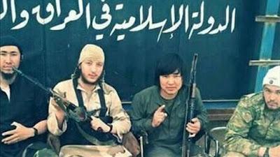 Dos combatientes chinos ―uno sentado a la izquierda y el otro en el centro― del grupo terrorista EIIL.