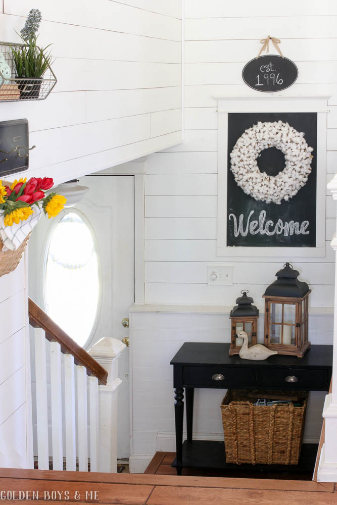 Farmhouse style entry with planked shiplap walls and DIY chalkboard