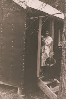 Alfreda and Stephen Olsen peeking out cabin door
