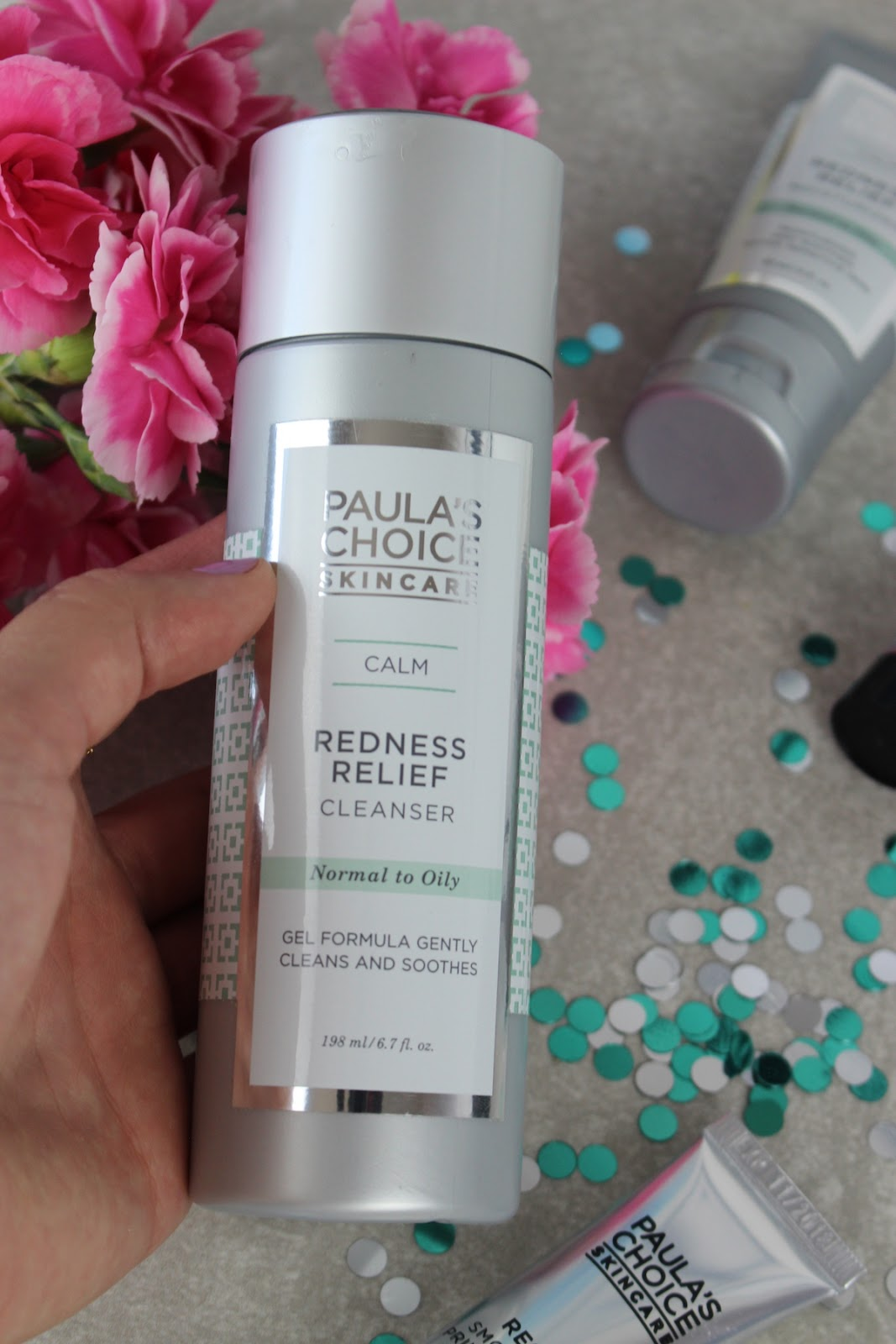 This is a close up of Paula's Choice Redness Relief Cleanser , surrounded by beautiful pink flowers.