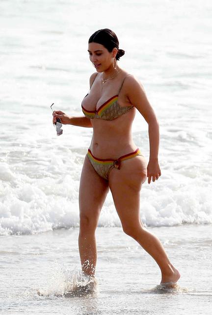 Kim berselulit berlarian di pantai