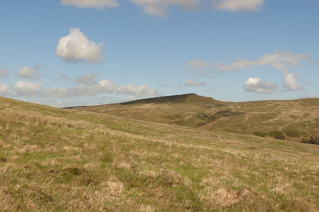 An escarpment on the horizon - blue sky above and a gently sloping hillside in the foreground.