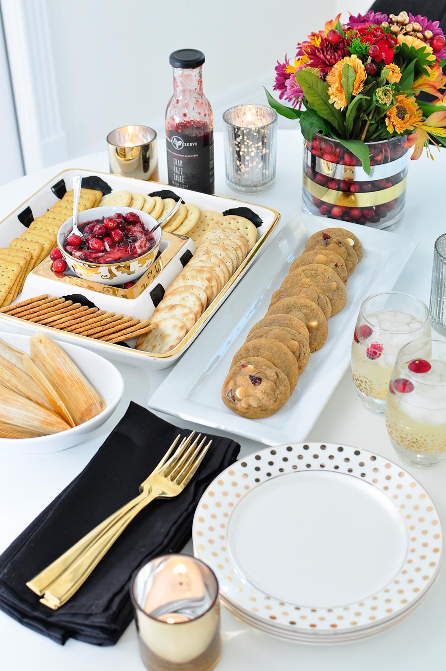 A black, white and gold Thanksgiving tablescape featuring cookies, tamales and a cranberry cream cheese dip appetizer.