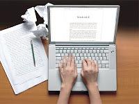 Bilgisayarında makale yazan bir yazar ve yanındaki kalem, notlar ve buruşturulmuş kağıtlar