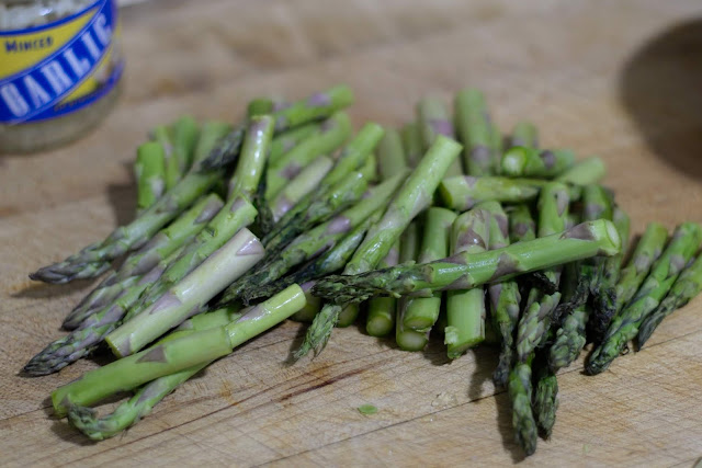 Fresh asparagus, cut up into bite-sized pieced, on a cutting board.
