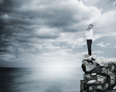 a man stands on a cliff and gazes over the ocean