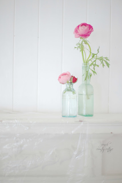 Ranunculus in jars with white paint on wood walls