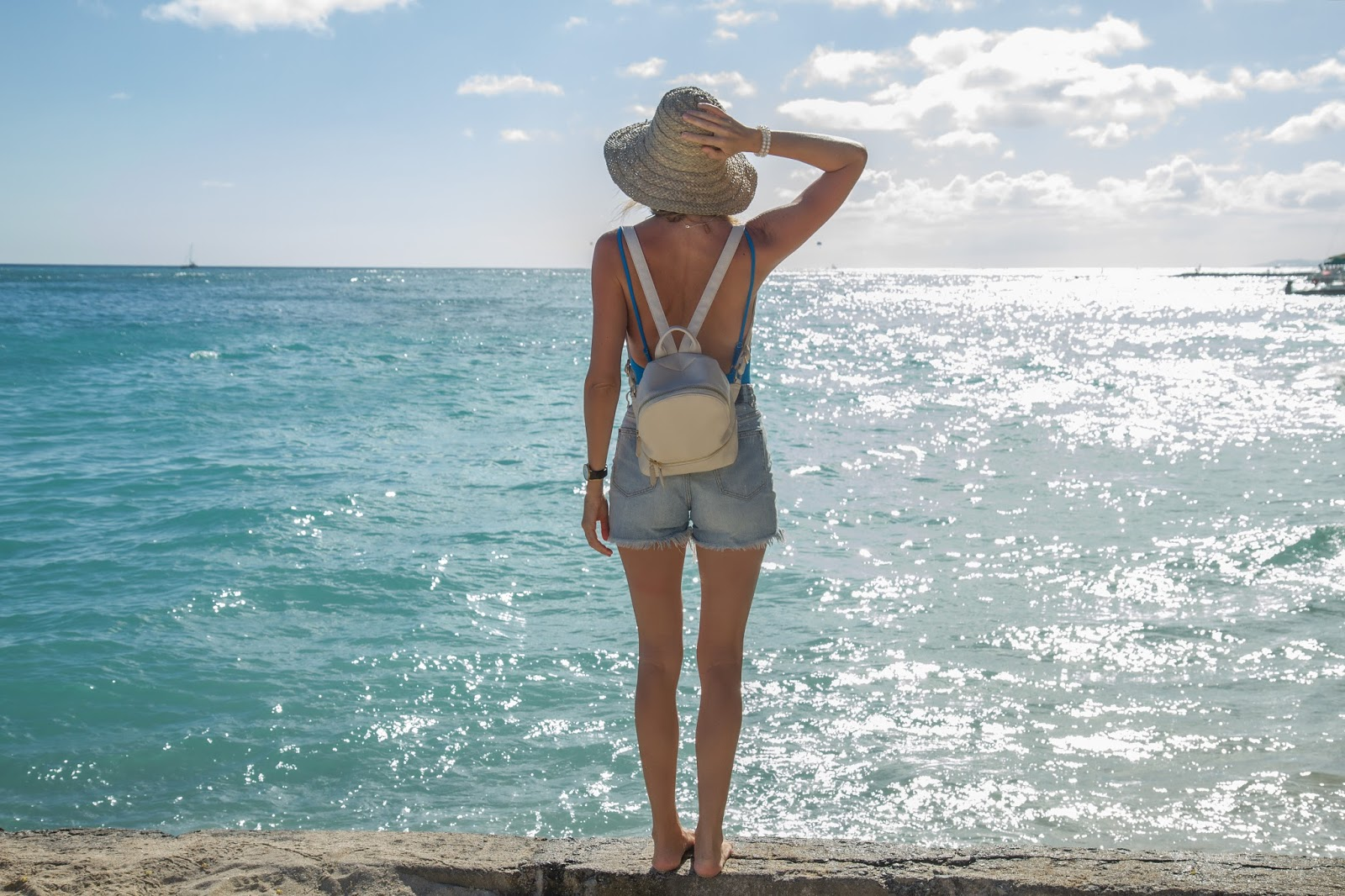 Fashion and travel blogger, Alison Hutchinson, is wearing a Solid and Striped swimsuit, Ksubi shorts, Saint Laurent Sunglasses and a wicker hat from Bali