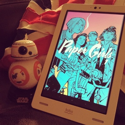 The cover of Paper Girls appears on a white Kobo. It features four girls of various ethnicities on their bikes, paused but ready to ride. The girls are coloured a flat, teal blue. The sky behind them is variegated pink and yellow. A small BB-8 model appears beside the Kobo, against a Union Jack pillow.