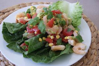 Tomato, corn and shrimp salad served on a white plate.