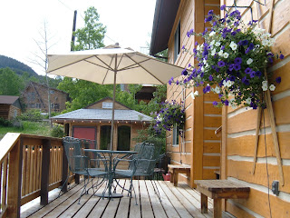 Sunny deck with chairs and a table leading to the gazebo with a hot tub, and a beautiful hanging basket with purple and white flowers.