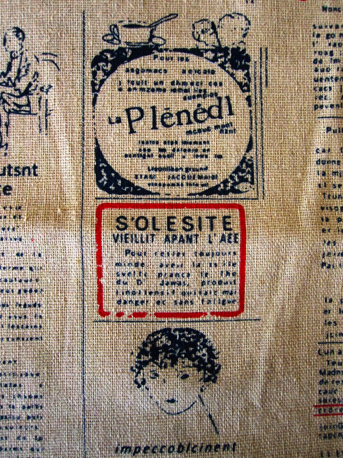 Close up of linen fabric printed with old french advertising in blue and red.