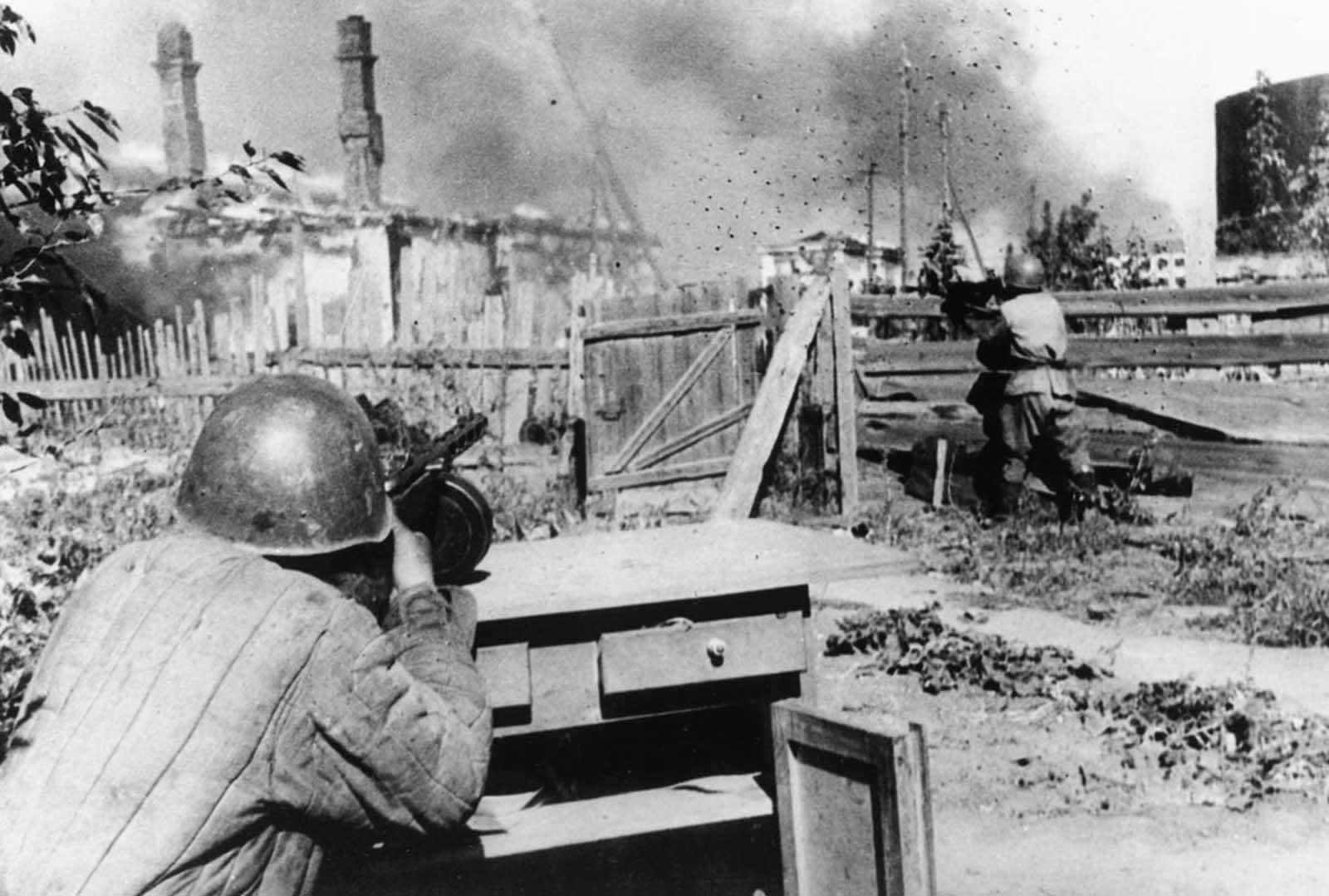 Standing in the backyard of an abandoned house in the outskirts of the besieged city of Leningrad, a rifleman of the Red Army aims and fires his machine gun at German positions on December 16, 1942.