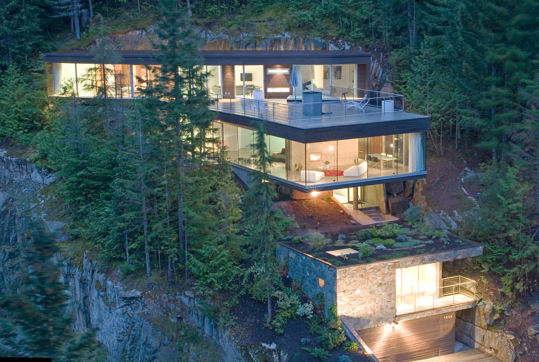The steep slope house design has a flat roof system that looks like frank lloyd wrights falling water only it performs much better and allows the snow to